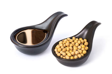 Tasty soy sauce with soy beans in black ceramic spoon isolated on white background. Banque d'images