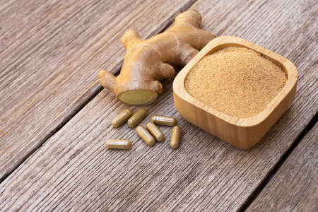 Fresh ginger slice and capsules with ginger powder in wooden bowl isolated on wooden table background. Herbal medicine plant and supplement concept.