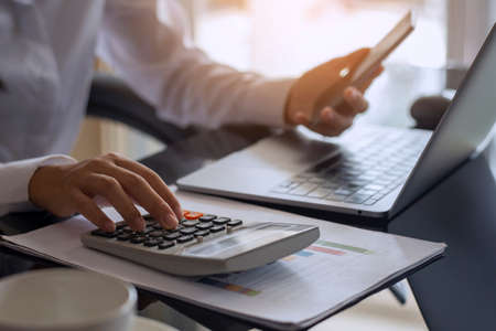 Casual business woman hand holdng credit or debit card and using calculator, work on laptop computer for online shopping and payment. e commerce concept. Top view. Imagens
