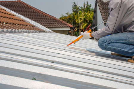 Worker man hand using glue gun with silicone adhesive or manual caulking gun with polyurethane to fix the metal steel on the roof. Installing and building construction concept.
