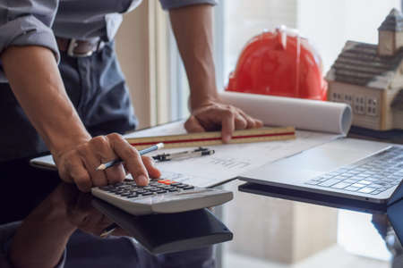 Architect man or male engineer hand using calculator and work on architectural project with laptop computer on the desk in office at workplace. Zdjęcie Seryjne