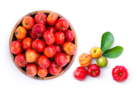 Closeup fresh small red organic acerola cherry fruit (Malpighia Glabra) with green leaf in wooden bowl isolated on white background.
