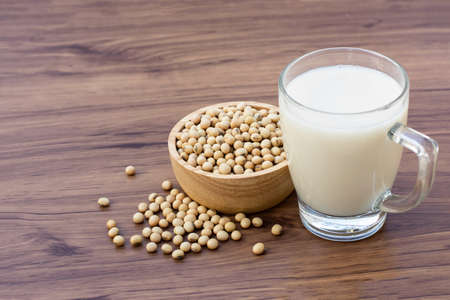 Soy beans in wooden bowl with glass of soy milk isolated on wood table background.