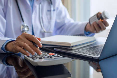 Female doctor in white lab coat,hand holding prescription medicine bottle and using calculator,work on laptop computer and notebook on the desk at office.