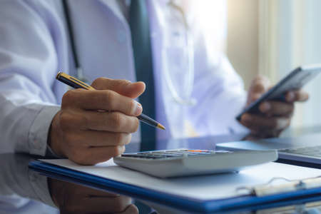 Male doctor hand hold pen, using calculator for calculate about medical costs and using mobile phone with laptop computer on the desk at office in clinic or hospital. Healthcare costs and fees concept