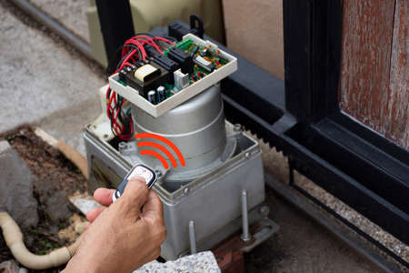 Technician man hand using remote control, testing and checking the functional of auto door. Maintenance and repairing automatic gate concept. service concept.