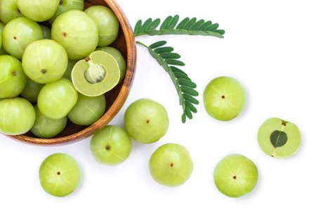 Closeup Indian gooseberry fruits ( phyllanthus emblica, amla ) in wooden bowl with green leaf and slice isolated on white background. Top view. Flat lay.