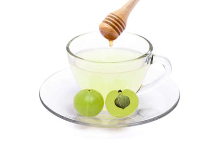 Closeup cup glass of Amla juice with fresh green Amla fruit or Indian gooseberry ( phyllanthus emblica ) with honey isolated on white background. 版權商用圖片