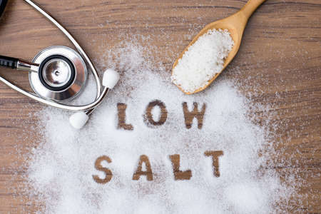 "White granulated natural sea salt in wooden scoop and words"" Low salt "" letters written in salt grains and medical stethoscope on wood table background. Unhealthy food concept. Top view. Flat lay."