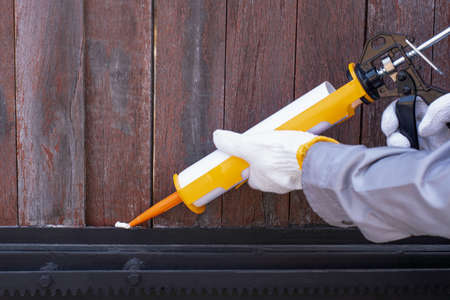 Technician man hand holding glue gun with silicone adhesive or manual caulking gun with polyurethane to repair and fix the metal steel to wood material. Installation and renovation concept.