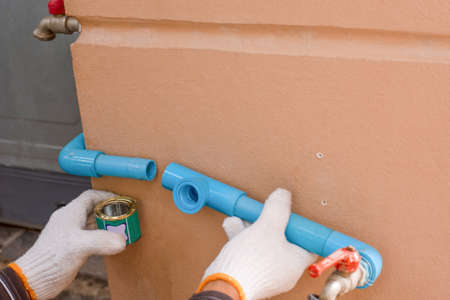Plumber hand weld blue plastic water pipe by using glue sealant. Stock Photo