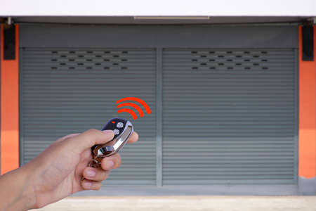 Closeup hand holding and using remote control to open the automatic shutter roller steel garage gate. Security system and wireless concept. Electronic door concept.