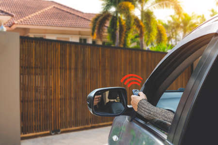 Woman in car, hand using remote control to open the auto gate when driving and arrive home. Automatic door, security system and wireless concept.