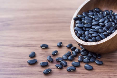 Black beans( Urad dal, black gram, vigna mungo ) in wooden bowl and scoop isolated on wood table background .