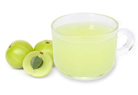 Closeup fresh organic Indian gooseberries fruit ( Amla ) and glass of gooseberry juice isolated on white background. Antioxidant fruit, herbal medicine plant and healthy drinks concept.