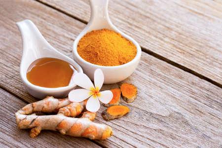 Tumeric ( curcumin, Curcuma longa Linn, turmeric ) powder in wooden bowl with rhizome and glass of honey isolated on wood table background. Beauty and spa concept.