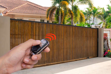 Man's hand holding and using remote control to open or close the automatic gate with car parking blurred background. Home remote control and electric door concept.