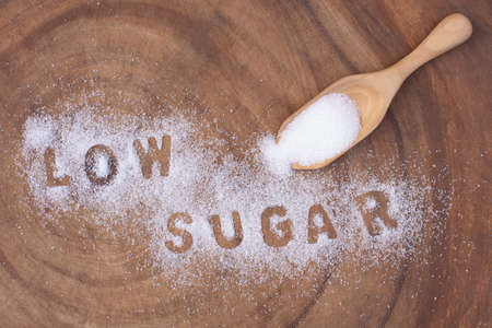 """White sugar in wooden scoop and words"""" low sugar """" letters written in sugar grains on wood table background. Healthcare,unhealthy diet and sugar free concept."""