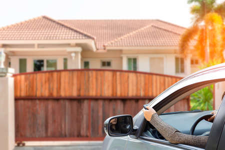 Woman in car, hand using remote control to open the automatic gate with modern home blurred background when arrived home. The electric door and home remote control auto door in concept.