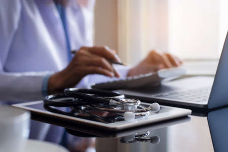 Doctor use calculator and work on laptop computer with medical stethoscope and digital tablet on the desk at office. Medical healthcare costs ,fees and revenue concept.