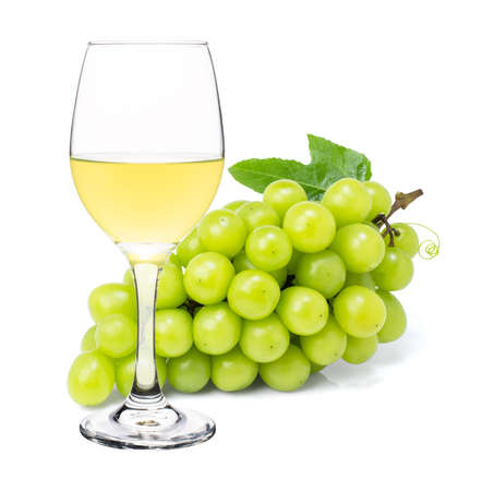White wine in vine glass with ripe grapes isolated on white background.