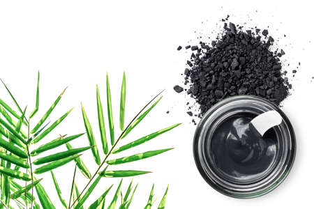 Charcoal powder and Clay or charcoal mud cream in jar with bamboo leaves isolated on white