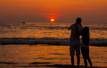 Silhouette of Romantic couple on the beach enjoying sunset photo