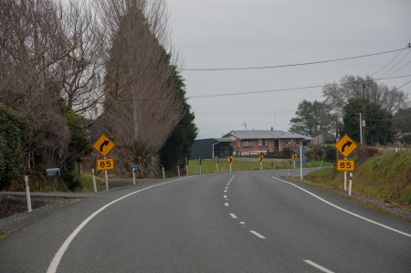 Bend ahead - Right turn at 85Km speed limit photo