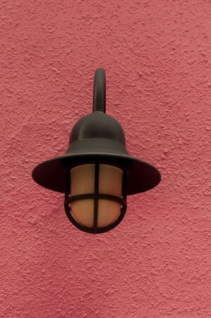 Black lamp post isolated on a red background photo