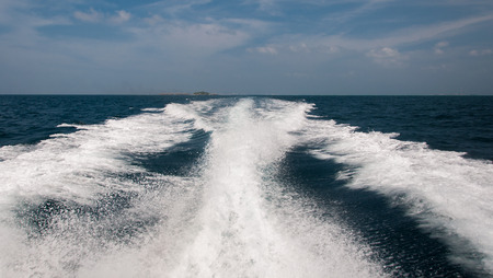 Foamy water spray from the back of the speed boat