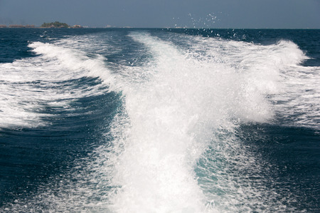Foamy water spray from the back of the speed boat photo