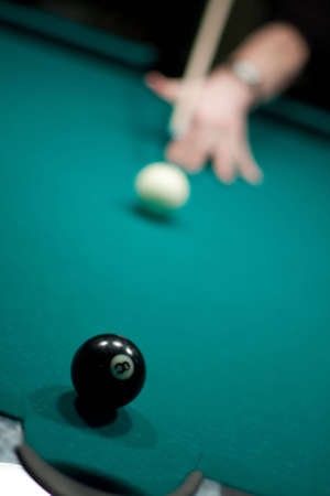 Cue in the hand, white ball and eight ball before final strike