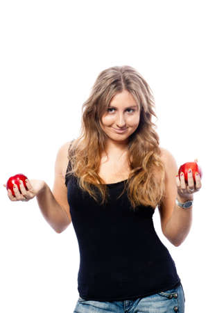 estimating: A pretty young blondie in a black top with brown charming eyes juggling two red apples, one in each hand, comparing and estimating them and offering you to taste them. White background, isolate ready.