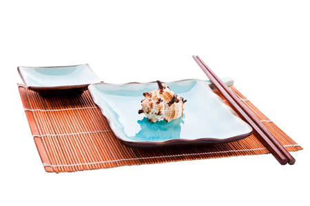 Traditional Japanese sushi tableware set: chopsticks on a rest, plate with a sea shell on it and a saucer, all on a bamboo place mat, on a white background, isolated.