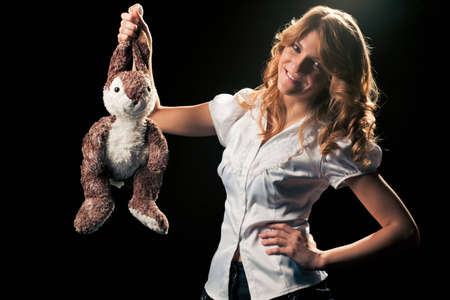 Pretty young grey-eyed blondie with a playful smile holding in her hand a toy rabbit suspended by the ears. Black background, ready for isolation Stock Photo - 8832346