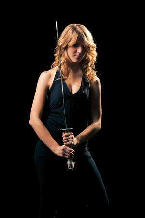 A young blondie in a black tight suit with a Japanese samurai sword in her hands ready to attack, on a black background.