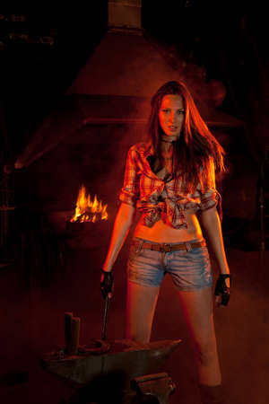 forge: Beautiful girl with long straight brown hair and smudgy face in a checkered shirt and jeans shorts with the fire irons in her hand standing near the anvil with a horseshoe on it in the center of the smoke-filled hot dim smithery with a burning furnace at