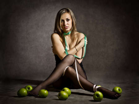 a sad pretty young blondie topless with a fear on her face wound herself with a centimeter measuring tape sitting at the floor in front of some green apples