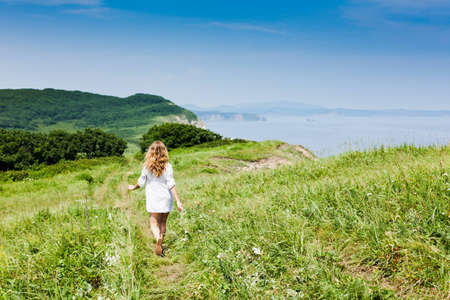 A blond-haired girl walking on a grassy track along a seaside towards a green hill, backshot