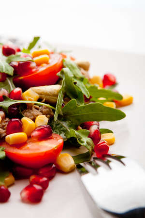 Tuna salad with rucola, tomatoes, sweet corn, cashew nuts and pomegranate grains. Shallow depth of field