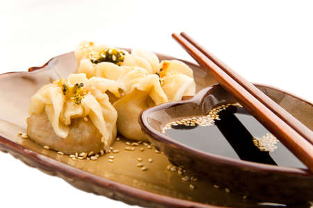 Three dim sum Asian steamed dumplings with broccoli, soybean and beancurd inside served in a traditional manner with sesame seeds, soy sauce and chopsticks, isolated on white Stock Photo