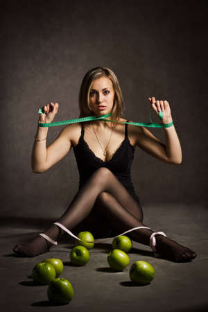 a pretty young blondie in a black top with a fear on her face stifling herself with a centimeter measuring tape sitting at the floor in front of some green apples photo