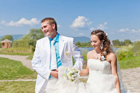 Bride and groom walking at countryside with a bouquet Stock Photo - 13497393