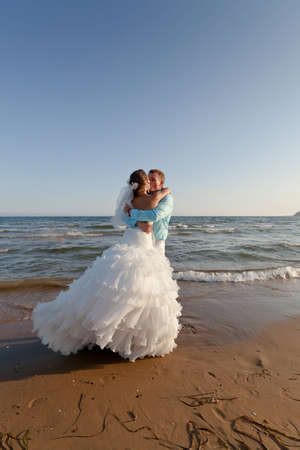 Bride in bridal dress and groom in white trousers and blue shirt kissing at the beach photo