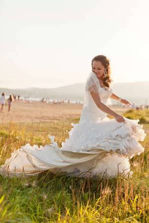 Bride plays with her messy dress at the beach at sunset