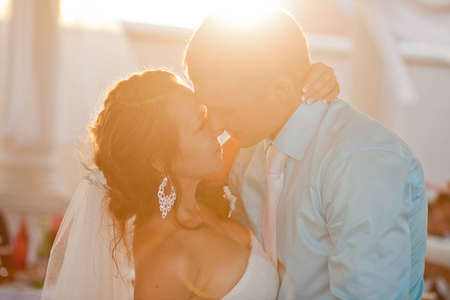 Happy kissing bride and groom in sunlight Stock Photo