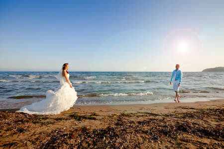 Bride in bridal dress and groom in white trousers and blue shirt at the beach at sunset