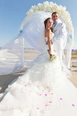 Bride and groom at the carpet in front of the arch of flowers photo