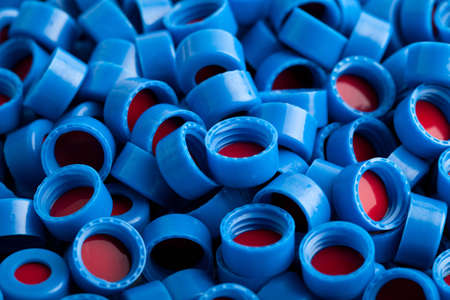 Background of blue and red carved plastic caps for chromatographic vials