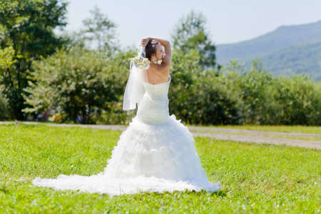 Beautiful bride with a bouquet looks behind standing at a green grass photo
